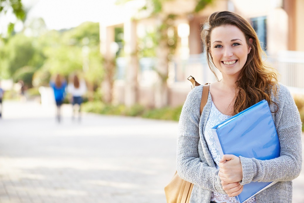 A female college student holding a notebook.